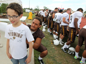 "Wyoming sophomore defensive end/outside linebacker Siaosi Hala'api'api signs the short of a young fan after the Cowboys practiced at Cheyenne Central High Saturday afternoon. The event was dubbed ""Cowboys in the Capital.""/Photo by Blaine McCartney, Wyoming Tribune Eagle"